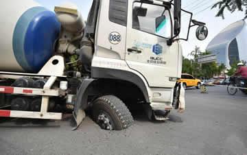 北京一水泥罐车压塌马路 前轮深陷动惮不得