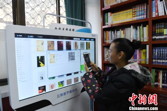 图为图书馆内的云屏借阅机,读者可以扫描二维码下载电子书籍阅读。 杨艳敏 摄