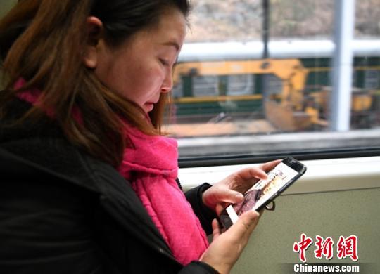 火车上李洪梅不停翻看手机上丈夫的照片。 刘忠俊 摄