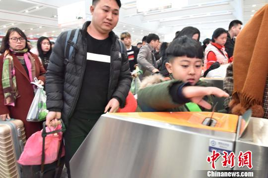 一名小旅客正在通过验票闸机。 郑智斌 摄