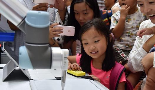 2018世界机器人大会:小朋友通过UR机器人画像绘画