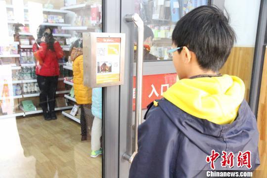 """一名小学生在入口处通过""""刷脸""""进入人工智能体验馆。 孙婷婷 摄"""