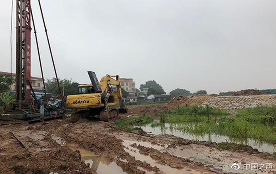 几位工人正在修理挖机