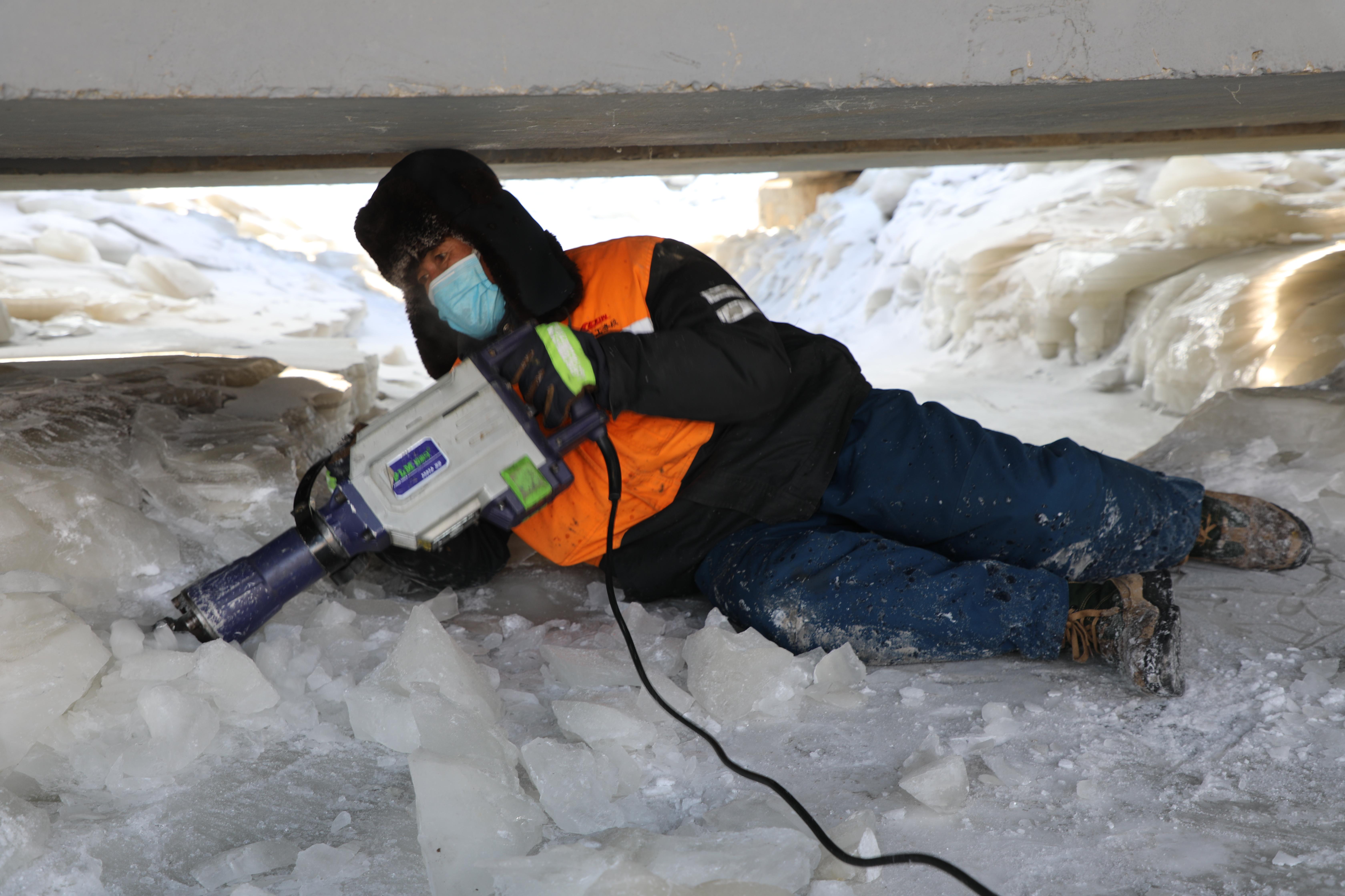 图2为桥梁工趴伏冰面上进行破冰作业 关贺贺摄.JPG