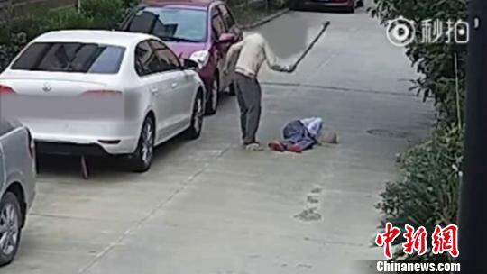图为:男子用拐杖抽打倒地老人身体。 视频截图 摄