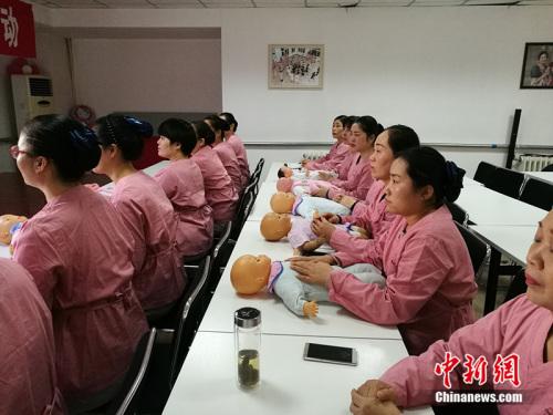 2016年12月15日,北京一家月嫂培训公司正在进行婴儿护理相关的实际操作训练。<a target='_blank' href='http://www.chinanews.com/' _fcksavedurl='http://www.chinanews.com/' ></table>中新网</a> 李卿 摄