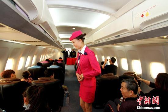 """资料图:机舱""""空姐""""为乘客服务。<a target='_blank' href='http://www.chinanews.com/' _fcksavedurl='http://www.chinanews.com/'></table>中新社</a>记者 张道正 摄"""