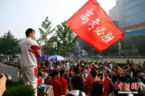 """资料图:2017年6月7日,北京人大附中考点外,学生挥舞""""高考必胜""""红旗为考生加油。<a target="""