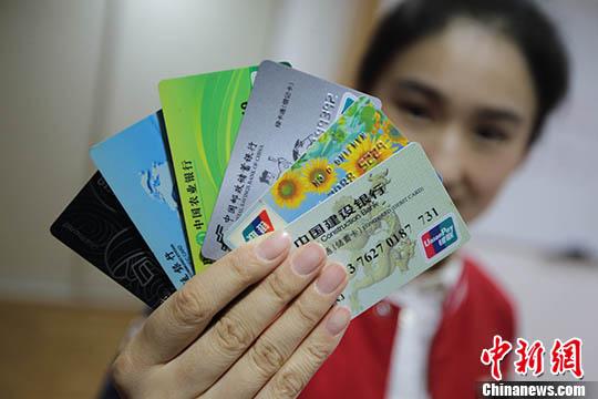 图为一位南京市民展示她所拥有的不同银行的银行卡。(资料照片) <a target='_blank' href='http://www.chinanews.com/' _fcksavedurl='http://www.chinanews.com/'></table>中新社</a>记者 泱波 摄