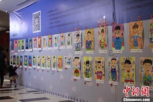 """资料图:为迎接父亲节,兰州百名孩童用稚嫩的画笔画出了自己""""心中的爸爸""""。徐雪 摄"""