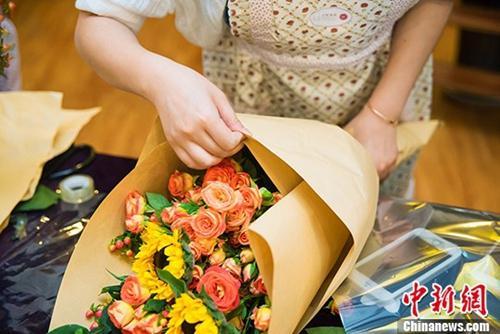 资料图:2016年6月19日是父亲节,武汉十余市民亲手插花献父亲表爱意。一位市民正在整理即将完成的花束。 周博 摄
