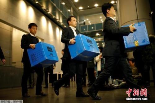 2016年11月8日,韩国检方突击搜查了三星电子在首尔的办公室,检察机关有关负责人将扣押物品箱子拿出来。