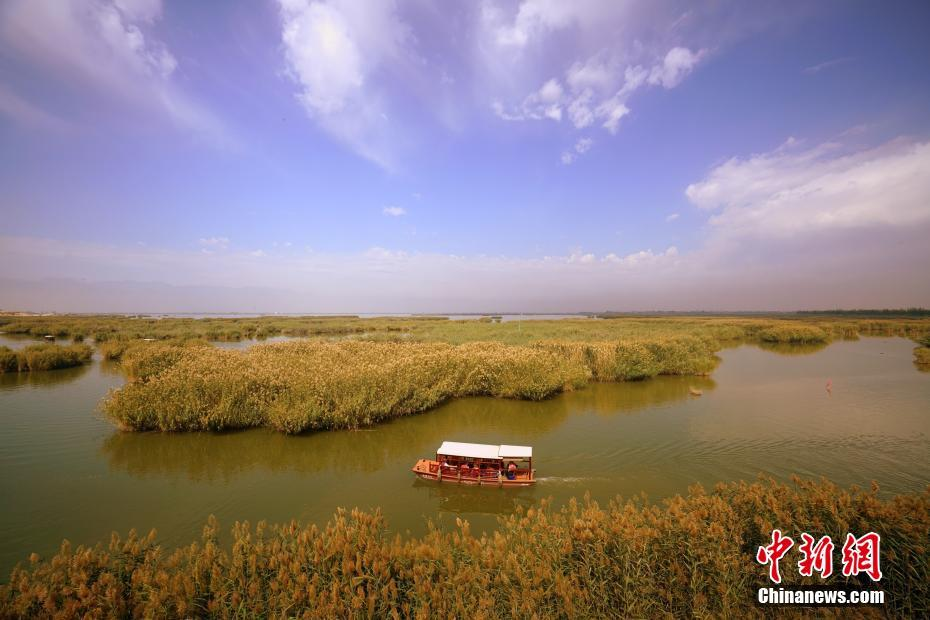 9月23日,游客乘坐游船在宁夏沙湖景区观光旅游。宁夏沙湖位于银川市以北38公里处,湖水、沙山、芦苇、飞鸟、游鱼等独特旅游资源有机结合,融江南秀色与塞外壮美于一体,素有塞上明珠之称。 中新社记者 张炜 摄