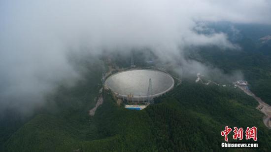 """7月3日,位于中国贵州省内的500米口径球面射电望远镜(FAST),顺利安装最后一块反射面单元,标志着FAST主体工程完工,进入测试调试阶段。FAST主动反射面由4450块反射面板单元组成,面积约25万平米,近30个标准足球场大小,用于反射无线电波。据介绍,FAST旨在实现大天区面积、高精度的天文观测,其科学目标包括巡视宇宙中的中性氢、观测脉冲星、探测星际分子、搜索可能的星际通讯信号等,其应用目标是在日地环境研究、搜寻地外文明、国防建设和国家安全等国家重大需求方面发挥作用。图为7月2日航拍安装完成前夕雾中的""""天眼""""。 <a target='_blank' href='http://www.chinanews.com/' _fcksavedurl='http://www.chinanews.com/'></p></table>中新社</a><p>  记者 贺俊怡 摄"""