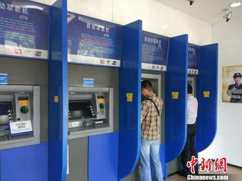 民众在自动取款机上取钱。<a target=