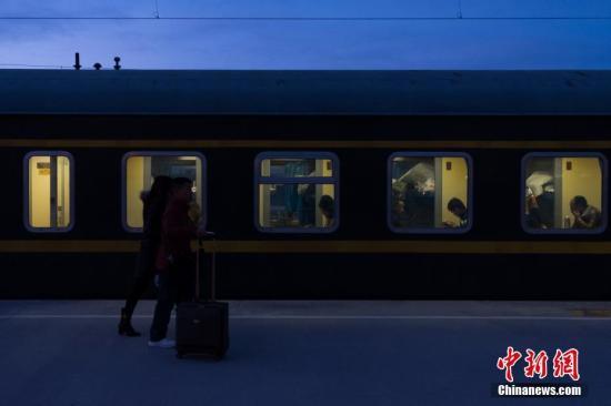 """2月13日清晨,从格尔木站上车返乡的旅客。历经21小时,1956公里的跋山涉水,由铁路拉萨站开往成都的Z324次列车,13日15时19分抵达西宁站,完成雪域""""天路""""――青藏铁路段的行驶,八百余名旅客顺利完成春运""""大迁徙""""。青藏铁路被誉为""""天路"""",起于青海省西宁市,途经格尔木市、昆仑山口,翻越唐古拉山口,最终抵达拉萨。是世界海拔最高、在冻土上路程最长的高原铁路。 <a target='_blank' href='http://www.chinanews.com/' _fcksavedurl='http://www.chinanews.com/'>中新社</a>记者 何蓬磊 摄"""