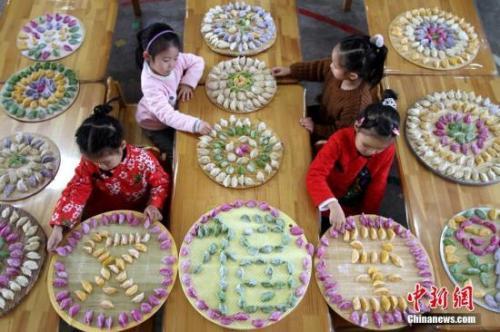 资料图:小朋友们在老师的带领下,用各种蔬菜汁和成彩色面团,一起包出多彩饺子,感知传统民俗文化。 <a target='_blank' href='http://www.chinanews.com/' _fcksavedurl='http://www.chinanews.com/'>中新社</a>发 胡高雷 摄 图片来源:CNSPHOTO