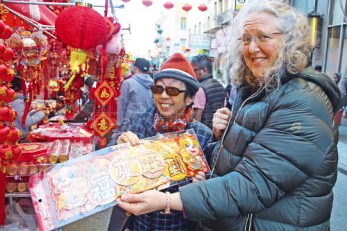 """近日,美国非华裔民众也在选购年货,拿着""""福来旺到""""的春联。(美国《世界日报》记者李晗/摄影)"""