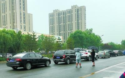 天宫院D口公交站,打着伞的揽客人和停在行车道上的黑车。 白歌 摄