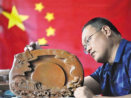 山西省新绛县,全国劳模、绛州澄泥砚研制所所长蔺涛在修饰建国系列砚台产品。 高新生摄(中经视觉)
