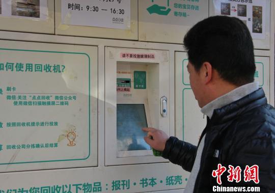 管理回收机的公司还定期在小区内免费集中地办理回收卡。图为一市民正在刷卡使用智能回收机。 赵晓 摄