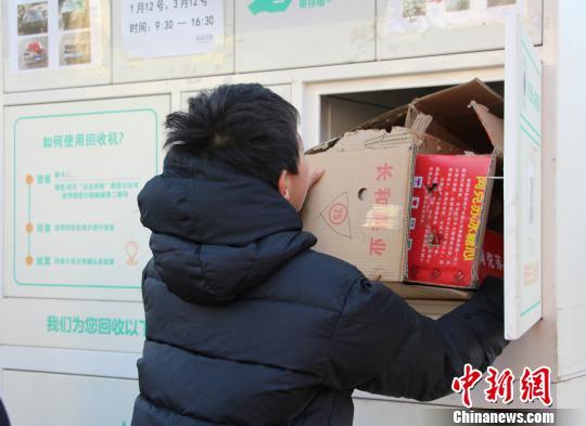 图为市民将整理好的废纸箱投入智能回收机的空箱,进行称重结算。 赵晓 摄