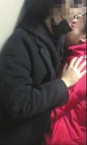 12日凌晨,捡狗女子何某(右)哭着抱住小吴道歉。