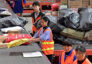 Workers sort parcels at express delivery company in China