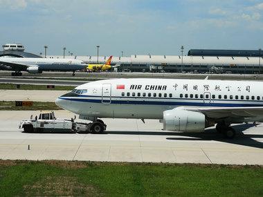 资料图:一辆飞机牵引车正牵引一架中国国际航空公司的飞机经过首都机场停机坪- 摄影 经济日报-中国经济网记者- 付云鹏.jpg