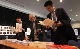 """在""""丝绸之路经济带财经智库国际研讨会""""前,与会嘉宾关注经济日报和中国经济网的会议资料.jpg"""