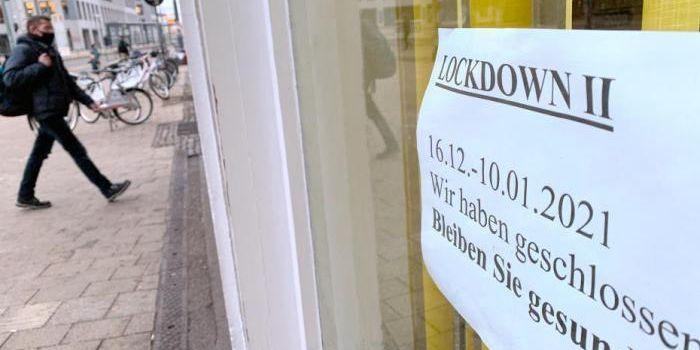 """1月5日,行人经过德国柏林一家已经关闭的花店。该店橱窗上张贴有""""由于第二轮封城关闭""""的告示。 中新社记者 彭大伟 摄_副本.jpg"""