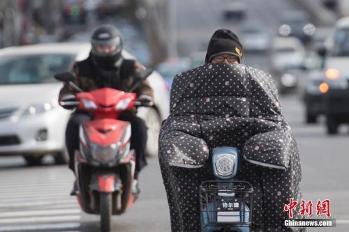 """11月10日,山西太原,民众出行时纷纷""""全副武装""""抵御寒风侵袭。 韦亮 摄"""