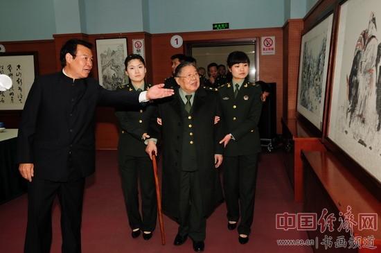 柯杨稳(左)向李铎(中)介绍他的绘画