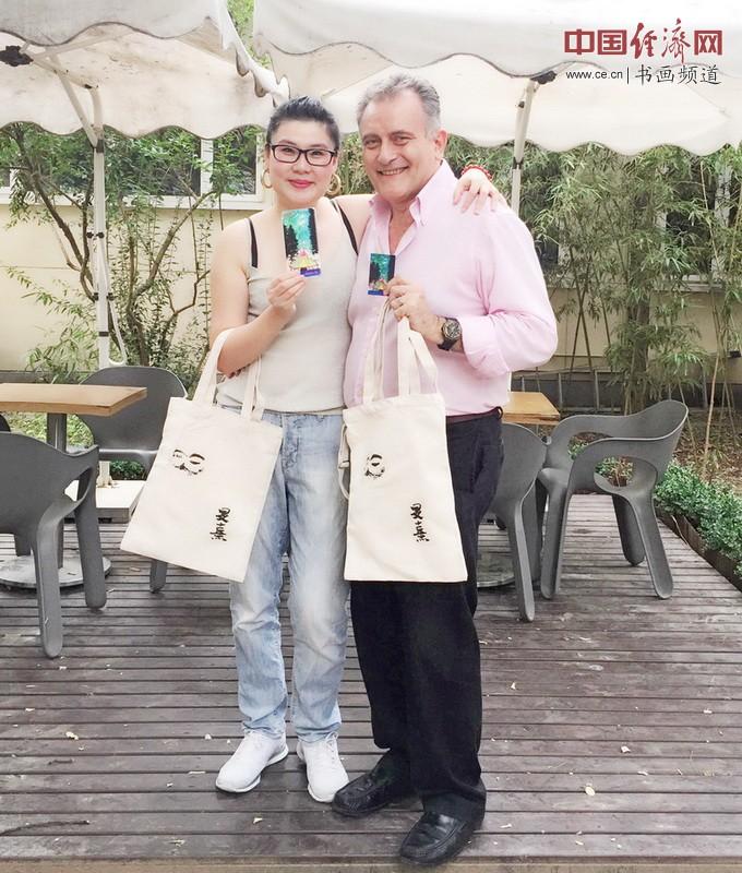 何�F熹(Anika He)和意大利朋友Bellico Marcello手持的艺术延伸品布包和手机壳