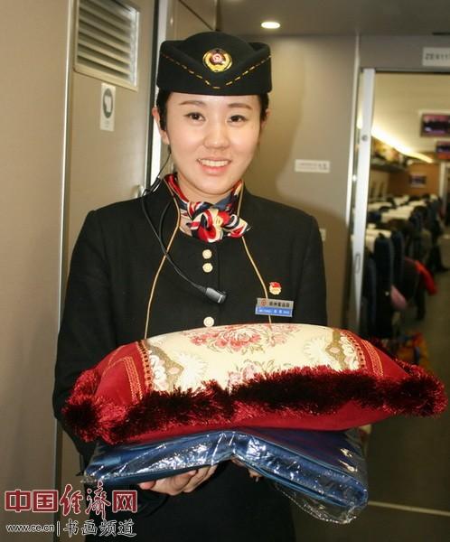 列车员赵璐手持物品前往整理车厢座位