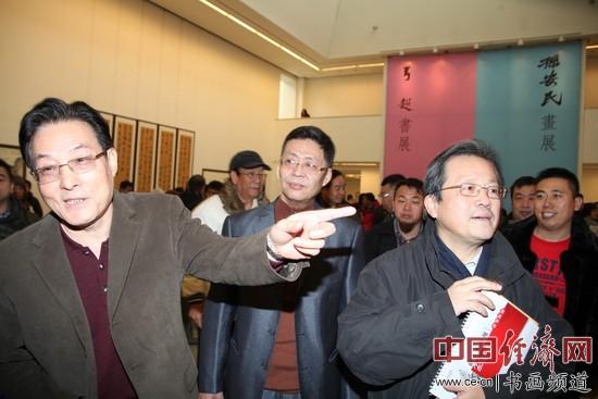 冯远(右)、孙安民(左)、弓超(中)等人在现场观赏书画作品李玉生摄