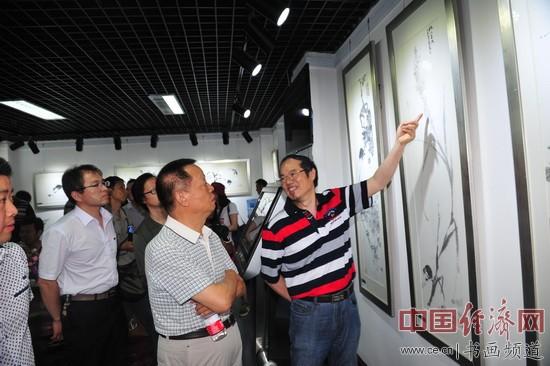 周逢俊(右)为嘉宾讲解他的国画