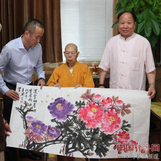 国画大家刘天明(右)与一诚法师(中)手持《富贵吉祥长寿图》合影