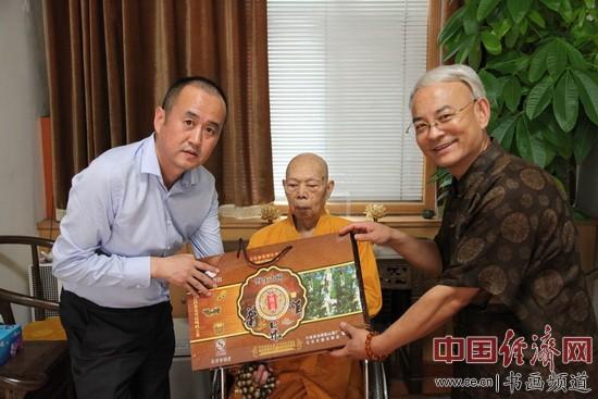 易经实用学家王粤生(右)代表北京乐源玉茶庄向一诚法师(中)赠送千年古树普洱茶并祝福