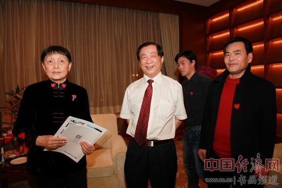 国画大师吴东魁(中)与李泽存(右)一起向有关领导赠送画册