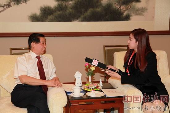 国画大师、慈善大使吴东魁(左)在贵宾室接受电视台采访