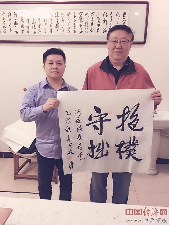 中国作协副主席高洪波(右)为冯磊(左)题书法