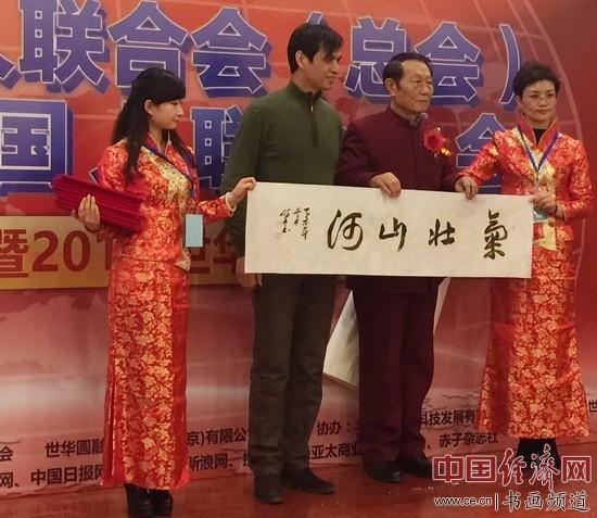 世界华人联合会(总会)主席夏荣怀先生(右二)在主席台上接收书画大家郑碎孟(左二)书法作品《气壮山河》