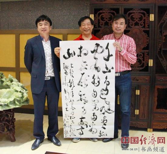 吴东魁(中)写书法与洛阳古典红木家具博物馆董事长周义新(右)、周学江(左)合影