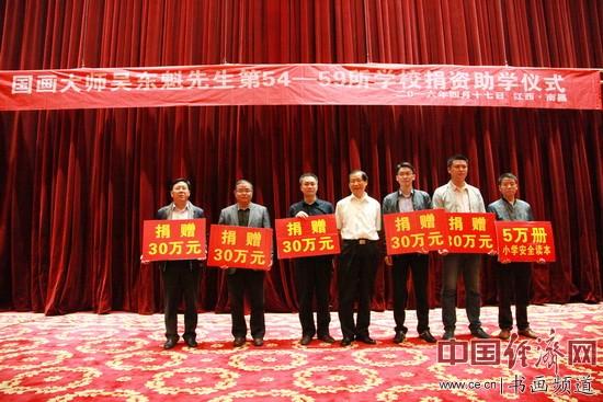 捐赠仪式上,国画大师吴东魁(中)向受赠学校捐赠资金,学校代表接收。