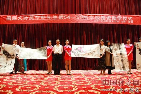 捐赠仪式上,国画大师吴东魁(中)捐赠价值不菲的国画作品并现场展示。