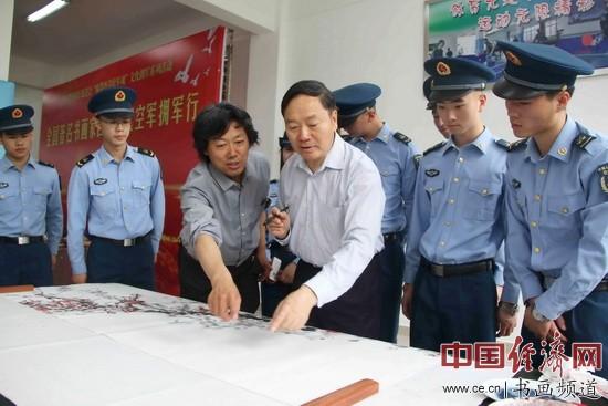 中国爱国拥军促进会会长罗平飞和书画家丁杰为官兵示范书写