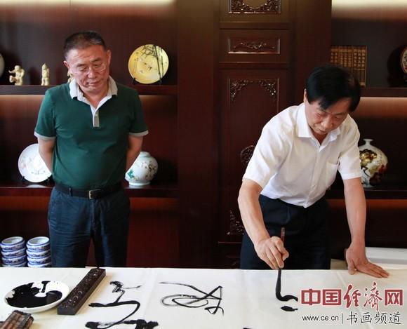 吴东魁(右)为伏羲庙题写书法作品,天水市市委书记王锐(左)陪同。
