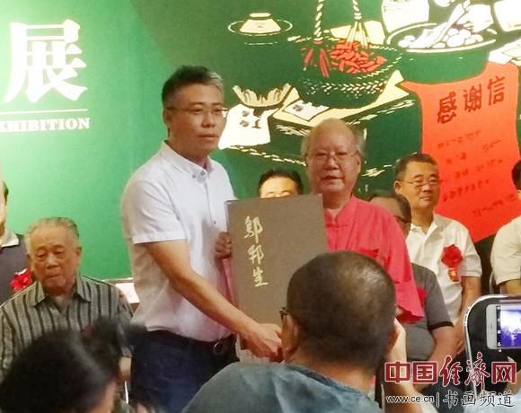 邬邦生(右)向81美术馆赠送画册,81美术馆执行馆长郭兴华(左)接收。中国经济网记者李冬阳摄